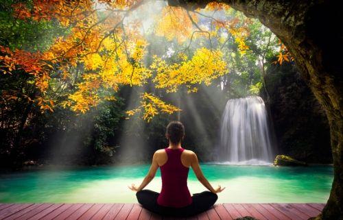 Femme qui médite, vue de dos, au bord d'une cascade