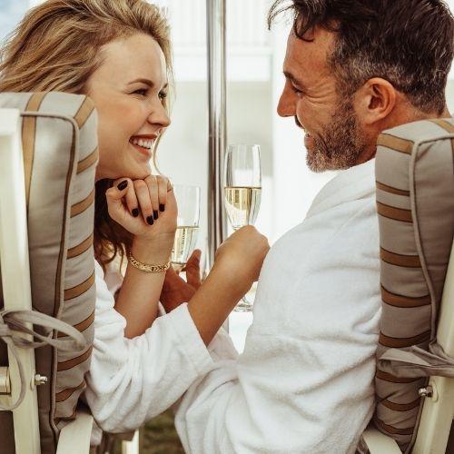 couple assis sur transat et qui trinque avec une coupe de champagne