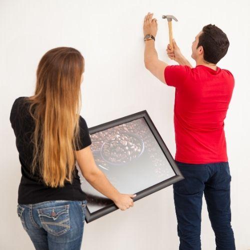 un homme plante un clou au mur pour poser le cadre de sa femme