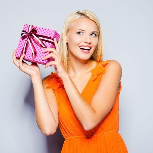 femme blonde qui reçoit un cadeau et est heureuse