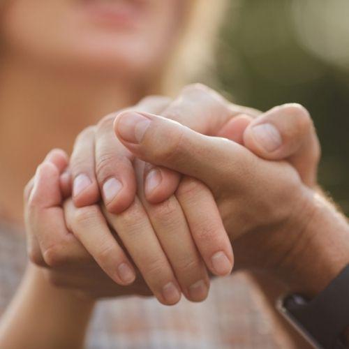 une main féminine entre les deux mains de son homme